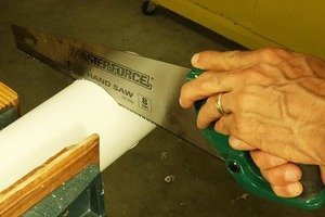Cutting PVC with a hand saw.