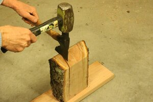 Splitting the natural wood log using a hatchet and a hammer.