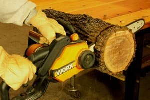 Cutting a log with an electric chainsaw.
