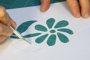Cutting out homemade flower stencil using an exacto knife.