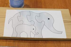 Adhere jigsaw puzzle pattern to wood.