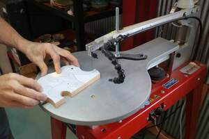 Use a scroll saw to cut out your wooden jigsaw puzzle pieces.