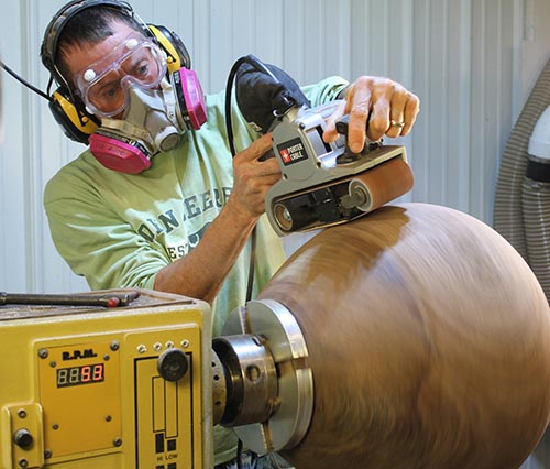 Sanding the exterior of a bowl using a belt sander.