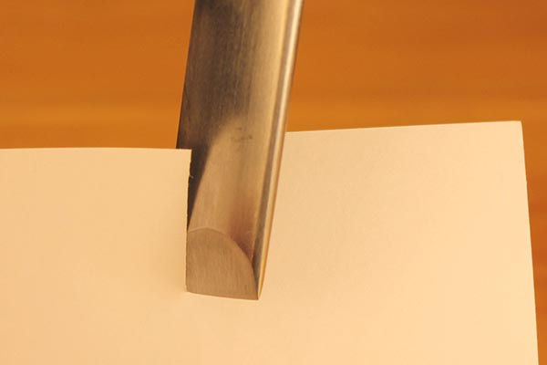 Testing the sharpness of an edge by cutting a piece of paper.