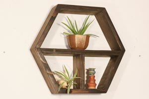 Honeycomb wall shelf with center shelf and vertical upright.