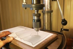 2B.  Drill pilot holes in wood using a drill press.