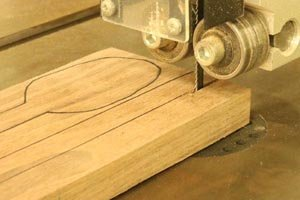 Cut out wooden spoon blanks on band saw.