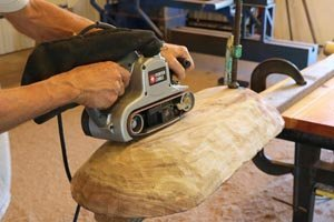 Using a belt sander to smooth the outside of the dough bowl.