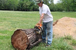 Using chainsaw to create straight edge on log for dough bowl.