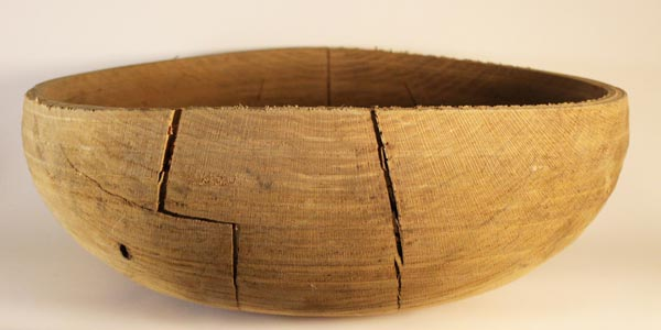 An oak bowl with massive cracks.