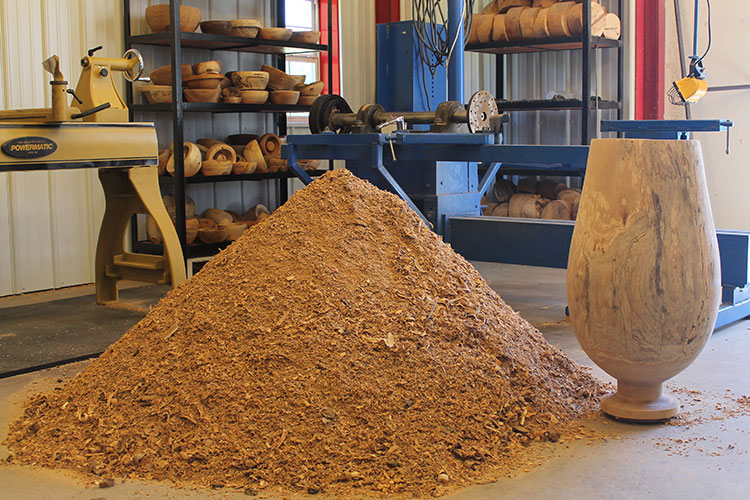 Creating a large sycamore vase. The final piece along with the pile of wood chips created by turning it.