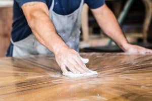 Sanding a wooden table by hand using sandpaper.
