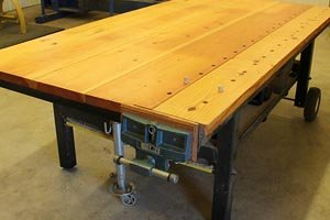 Workbench with wooden top, metal base, wheels, and jack.
